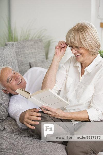 Lächelndes Seniorenpaar mit Buch auf Sofa im Wohnzimmer
