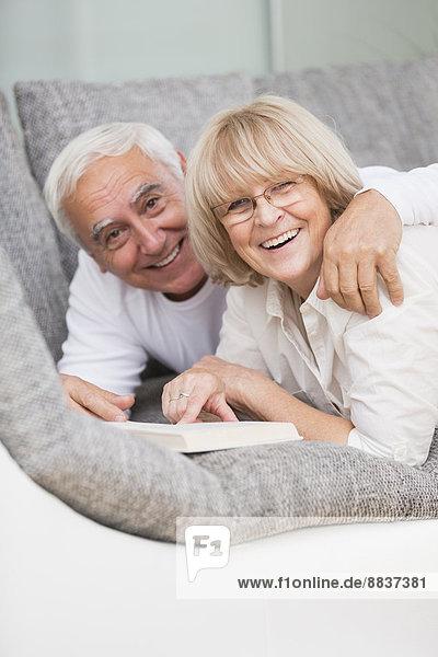 Porträt eines lächelnden Seniorenpaares mit nebeneinander liegendem Buch auf Sofa