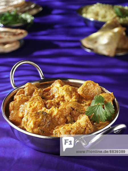 METAL DISH WITH CHICKEN KORMA PURPLE TABLETOP WITH NAAN BREAD SAMOSAS AND RICE