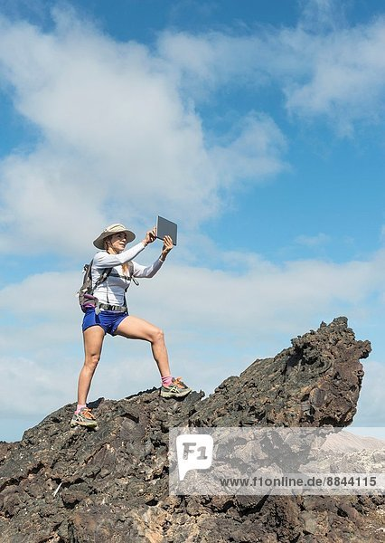 Tourist using a Tablet at Timanfaya National Park  Lanzarote  Canary Islands  Spain.