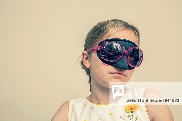 Preteen blond girl wearing a mask and sunglasses.