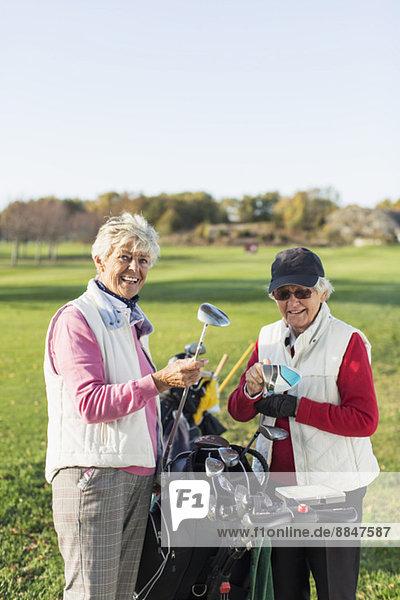 Glückliche Seniorinnen mit Schlägern auf dem Golfplatz