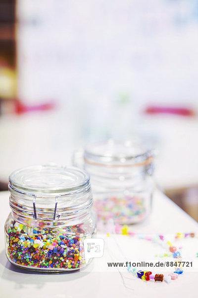 Gläser voller Perlen mit Halsketten auf dem Tisch im Kindergarten Gläser voller Perlen mit Halsketten auf dem Tisch im Kindergarten