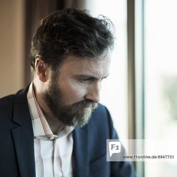 Businessman looking down by window in hotel room