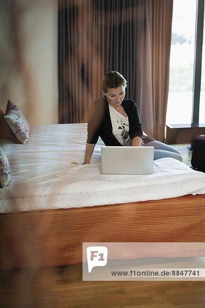Geschäftsfrau mit Laptop am Bett im Hotelzimmer