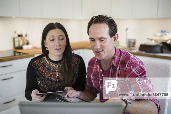 Paar mit digitalem Tablett mit Laptop in der Küche