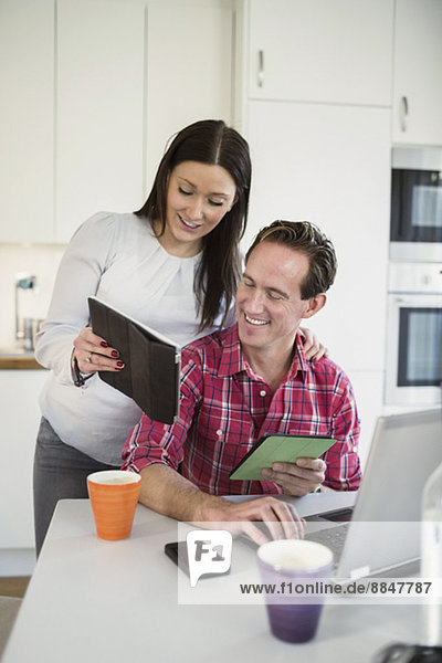 Couple using technologies at table in kitchen