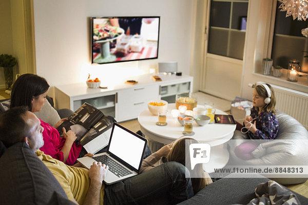 Familie mit Technologien im Wohnzimmer