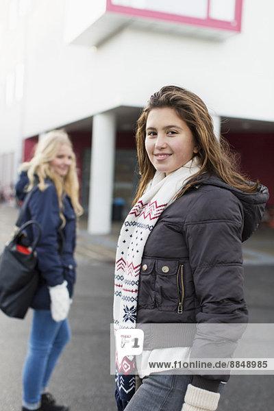Portrait of happy teenage girl in warm clothing on high school campus