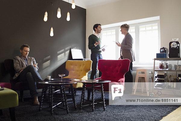 Geschäftsmann sitzend  während Kollegen im Büro diskutieren