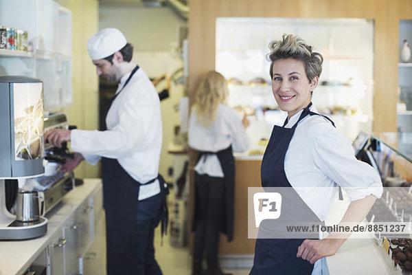 Porträt der lächelnden Cafébesitzerin mit Kollegen im Hintergrund