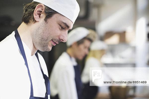 Seitenansicht des Bäckers in der Küche der Bäckerei