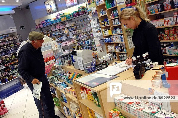 An elderly man sits and waits to collect his prescription at a chemist shop.