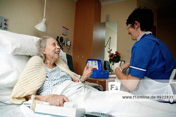 A senior nurse takes a pin prick of blood from the finger of an elderly patient. The nurse is collecting a small sample for a glucose test. The test is performed regularly for diabetics to enable monitoring of blood glucose levels to allow for the diabeti