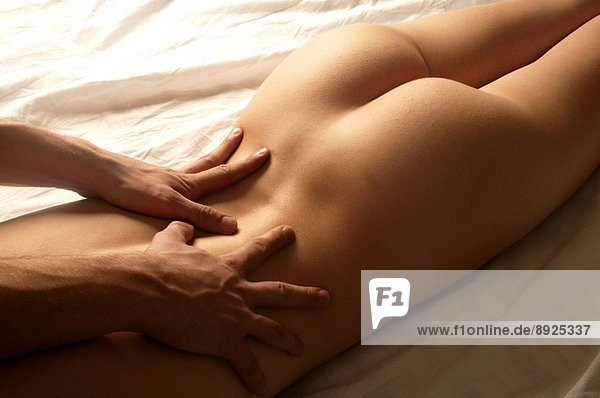The hands of a man massaging a young woman´s lower back while she is laying on her stomach.