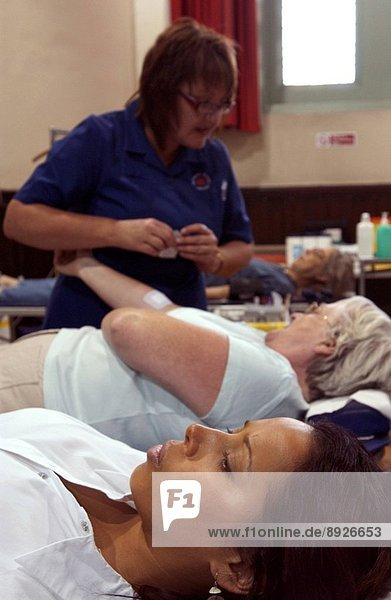 Women blood donors being attended by a nurse at a NHS National Blood Service collection centre.