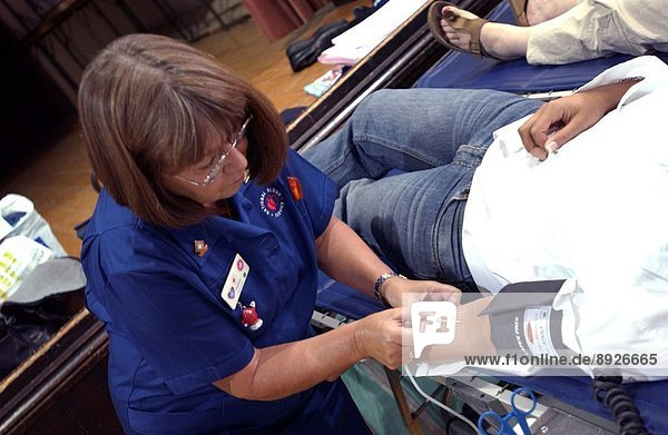 Female NHS National Blood Service nurse sterilizes the arm of a young woman donor before inserting a needle into the vein.