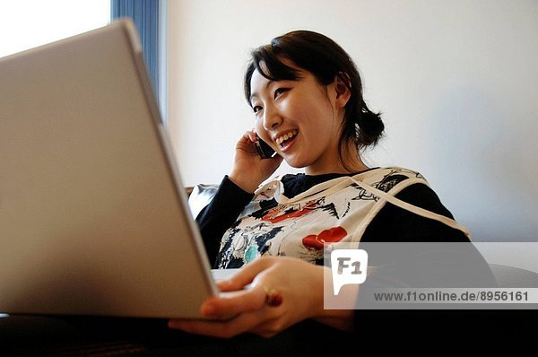 A young Asian woman  looking at a laptop computer  talking on a mobile phone.