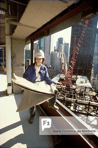Female Construction Worker Reading Blueprints
