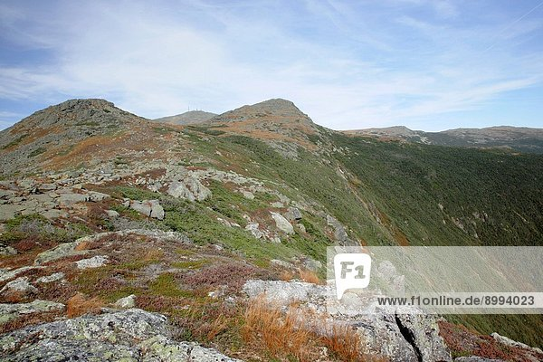 A hiker explores the summit of Whitewall Mountain during the autumn months. Located in the White Mountains  New Hampshire USA. Zeacliff can be seen in the background