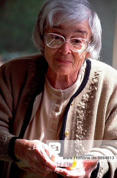 Elderly woman with magnifying glass suffering from Macular Degeneration  attempts to read her prescription drug bottles.