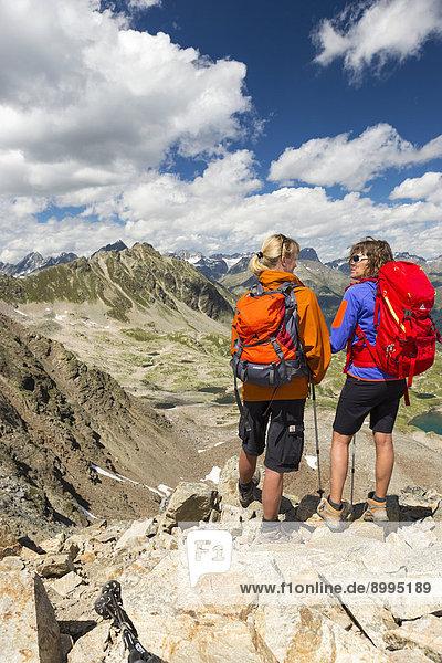 Two women hiking  Fuorcla da Barcli  views to the Macun lakes  Swiss National Park  Graubünden  Switzerland