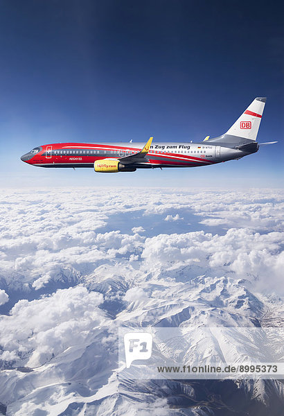 'TUIfly Boeing 737-8K5 WL  with the slogan ''Im Zug zum Flug''  German for ''take the train to the plane''  rail and fly  in flight over mountains  Turkey'