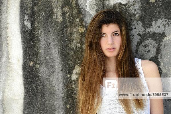 Mädchen mit langen Haaren  15 Jahre  steht an einer alten Wand  Portrait