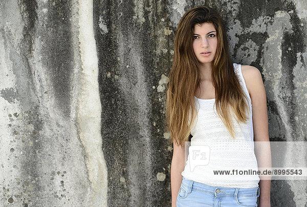 Mädchen mit langen Haaren  15 Jahre  steht an einer alten Wand