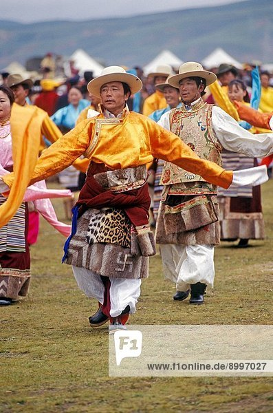 Male Khampa wears leopard skin  coral  zee stones & gold gau boxes at the Litang Horse Festival _ Sichuan Province  China  Tibet
