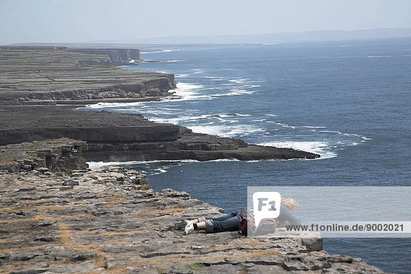 Woman peering over edge of sheer cliff D´n Aengus fort Inishmore  Aran Islands  County Clare  Ireland