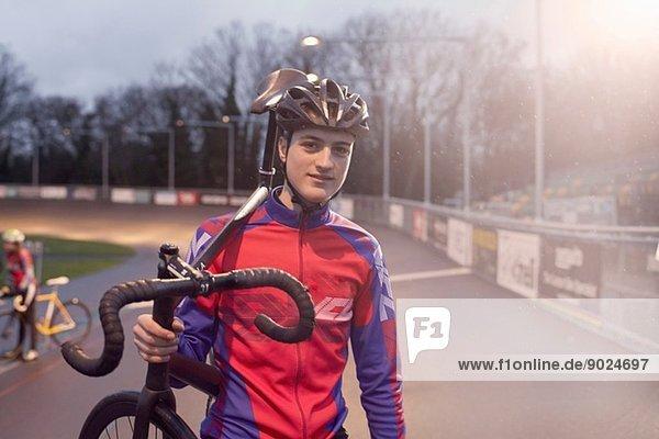 Porträt eines jungen Radfahrers mit Fahrrad auf dem Velodrom