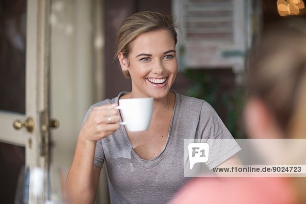 Zwei junge erwachsene Freundinnen beim Plaudern im Cafe