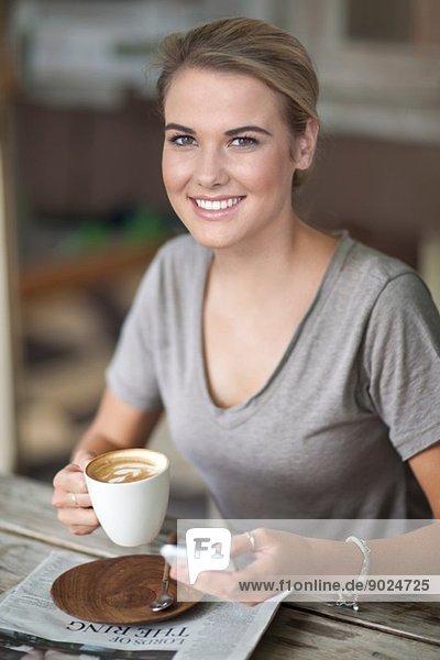 Porträt einer jungen Frau im Café mit Kaffeetasse und Handy
