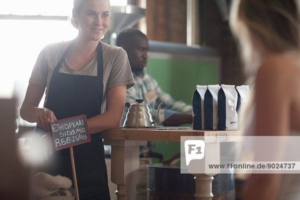 Young female waitress advising on coffee choice in cafe