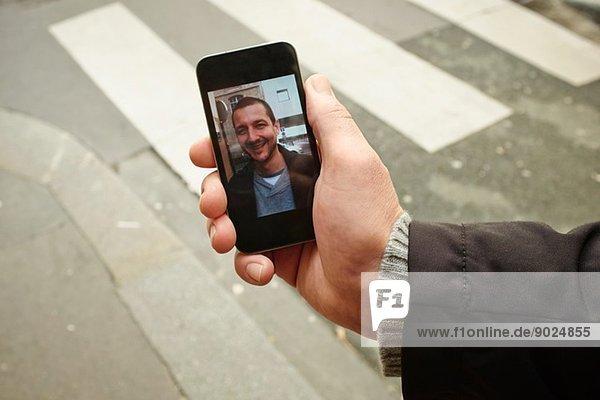Mid Erwachsene Mann auf dem Bürgersteig halten Smartphone mit Foto auf dem Bildschirm