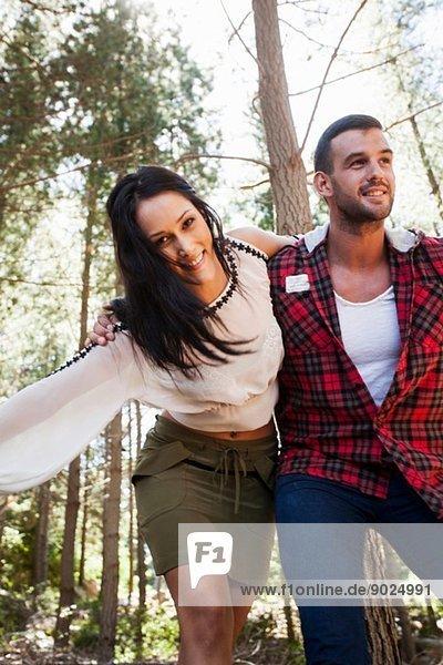 Ein junges Paar  das im Wald herumalbert.
