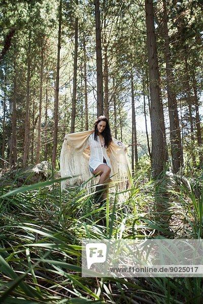 Junge Frau geht durch den Wald