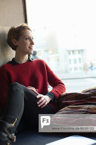 Frau am Fenster sitzend