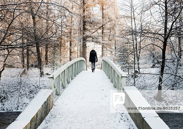 Frau überquert schneebedeckte Brücke  Rückansicht