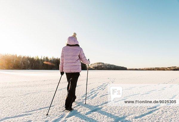 Frau Nordic Walking durch schneebedecktes Feld