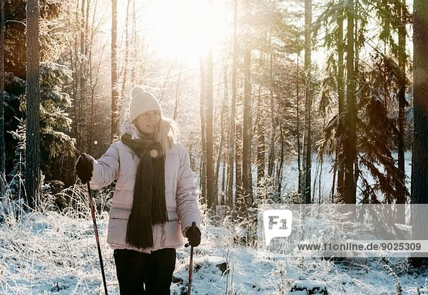 Mid adult woman nordic walking in snow covered forest