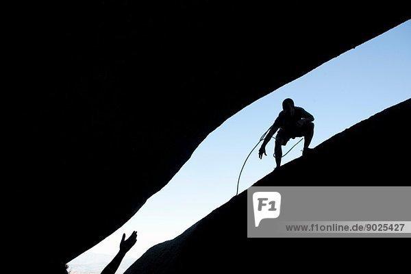 Silhouette junger  männlicher Kletterer  die auf dem Felsen aufeinander zugehen.