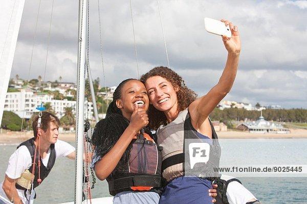 Zwei junge Freundinnen beim Selbstporträt mit Segelboot