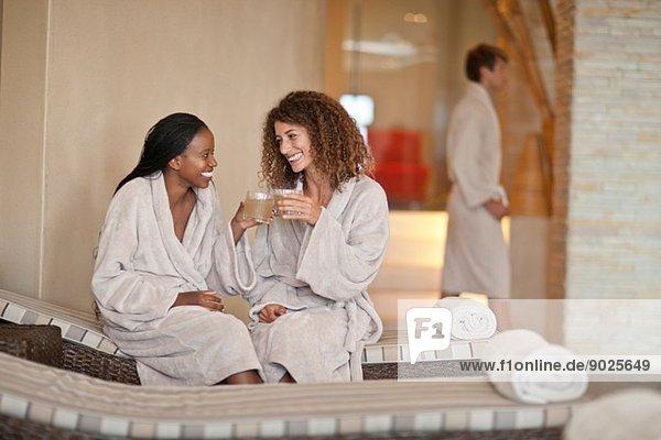 Zwei junge Frauen beim Plaudern auf Liegen im Spa