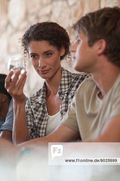 Mann und Frau sitzen am Tisch und probieren Getränke.