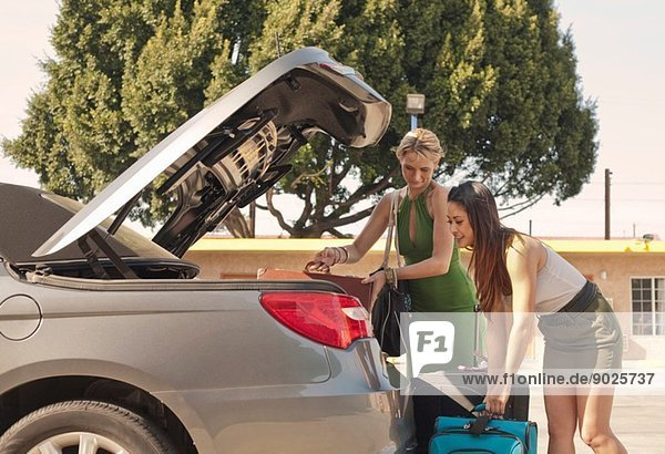 Junge Frauen stellen Koffer ins Auto