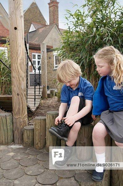 Schulmädchen beobachtet Jungen beim Schnürsenkelbinden am Holzzaun
