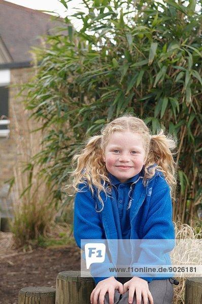 Porträt einer Schülerin im Garten sitzend