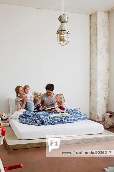 Familie mit drei Töchtern beim Lesen von Büchern im Bett
